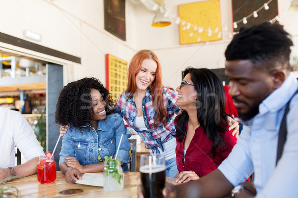 happy friends with drinks at bar or restaurant Stock photo © dolgachov