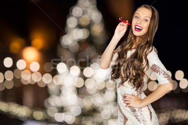 Kadın parti üfleyici noel ağacı ışıklar tatil Stok fotoğraf © dolgachov