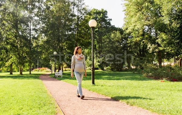 Felice incinta asian donna piedi parco Foto d'archivio © dolgachov