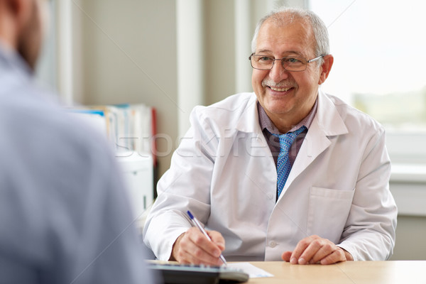 senior doctor talking to male patient at hospital Stock photo © dolgachov