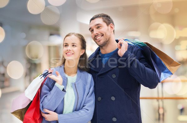 a5d961bc91 happy young couple with shopping bags in mall Stock photo © dolgachov
