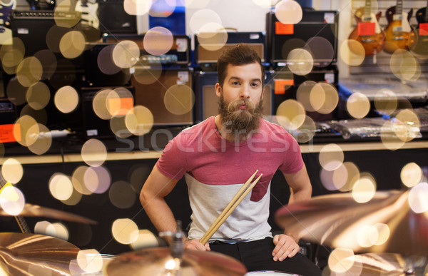 male musician with cymbals at music store Stock photo © dolgachov