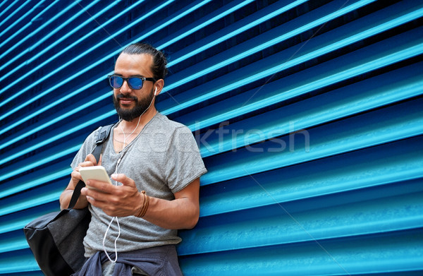 man with earphones and smartphone over wall Stock photo © dolgachov