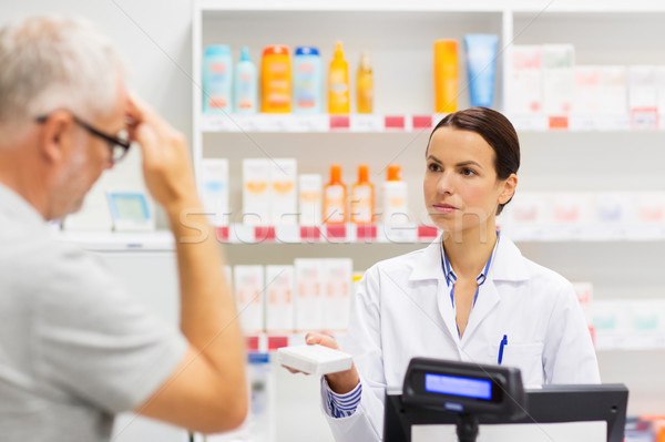 apothecary giving drug to senior man at pharmacy Stock photo © dolgachov