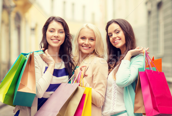 three smiling girls with shopping bags in ctiy Stock photo © dolgachov