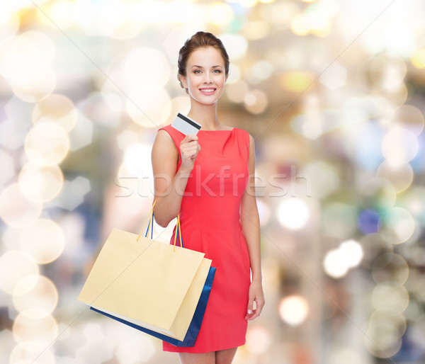 Stock photo: smiling woman with shopping bags and plastic card