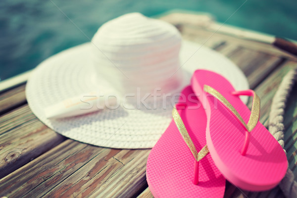 close up of hat, sunscreen and slippers at seaside Stock photo © dolgachov