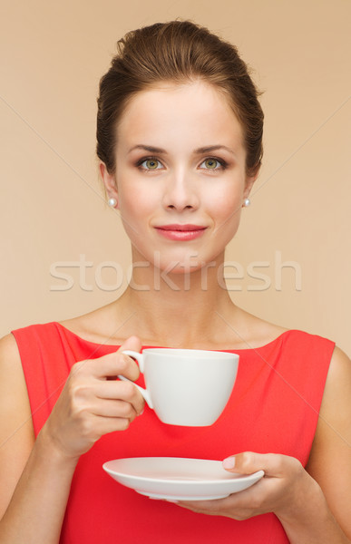 smiling woman in red dress with cup of coffee Stock photo © dolgachov