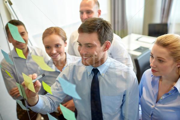 Souriant gens d'affaires marqueur autocollants travail d'équipe planification Photo stock © dolgachov