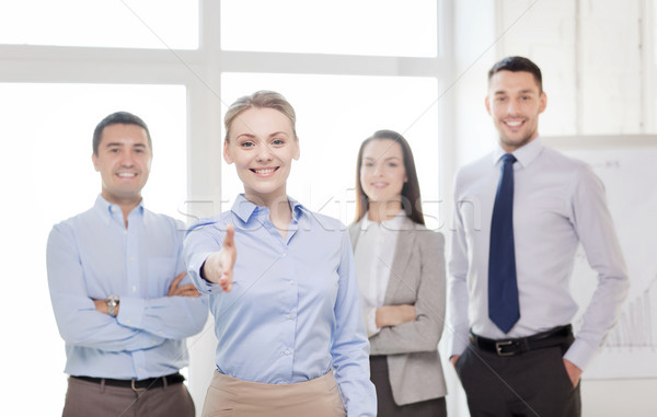 smiling businesswoman in office with team on back Stock photo © dolgachov
