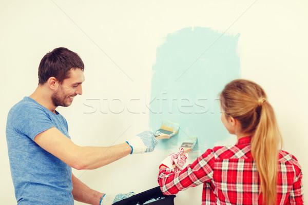 smiling couple painting wall at home Stock photo © dolgachov