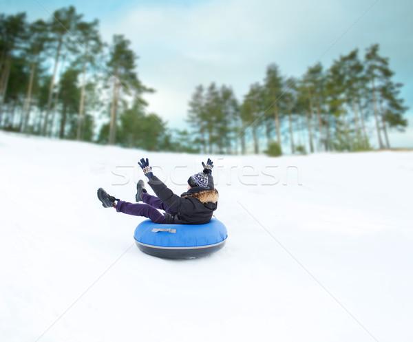happy young man sliding down on snow tube Stock photo © dolgachov
