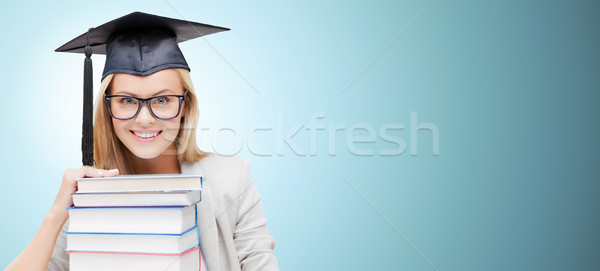 happy student in mortar board cap with books Stock photo © dolgachov