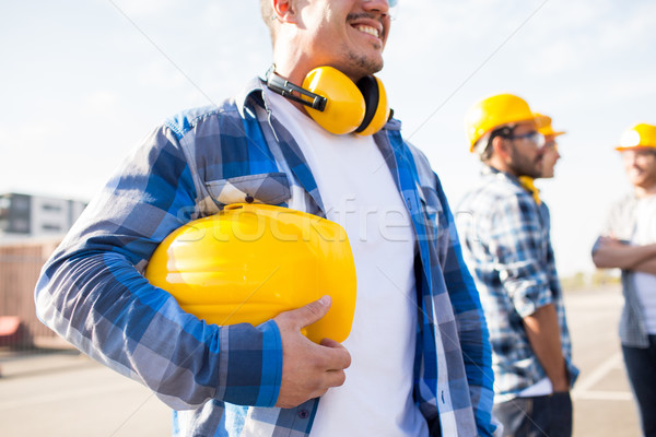 close up of builder holding hardhat at building Stock photo © dolgachov
