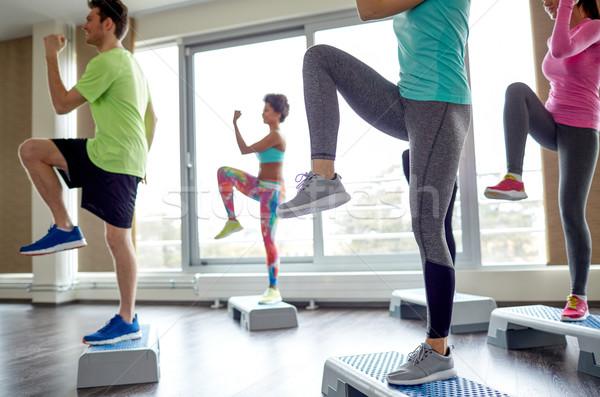 group of people raising legs on step platforms Stock photo © dolgachov