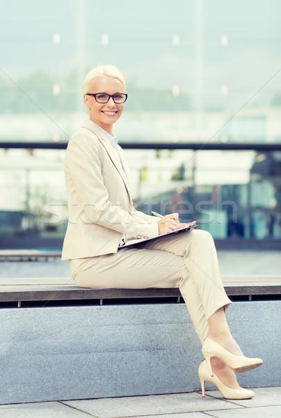 Jovem sorridente empresária bloco de notas ao ar livre pessoas de negócios Foto stock © dolgachov