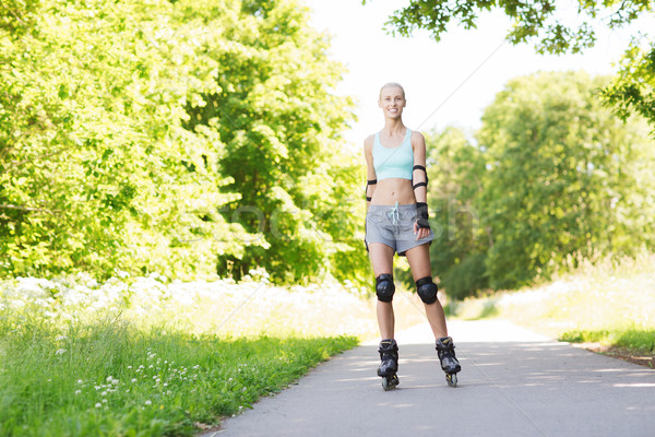 Stock photo: happy young woman in rollerblades riding outdoors