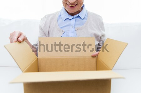 close up of senior woman with parcel box at home Stock photo © dolgachov