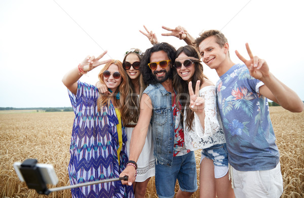 hippie friends with smartphone on selfie stick Stock photo © dolgachov