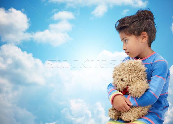sad little girl with teddy bear toy over blue sky Stock photo © dolgachov