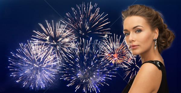 beautiful woman wearing earrings over firework Stock photo © dolgachov