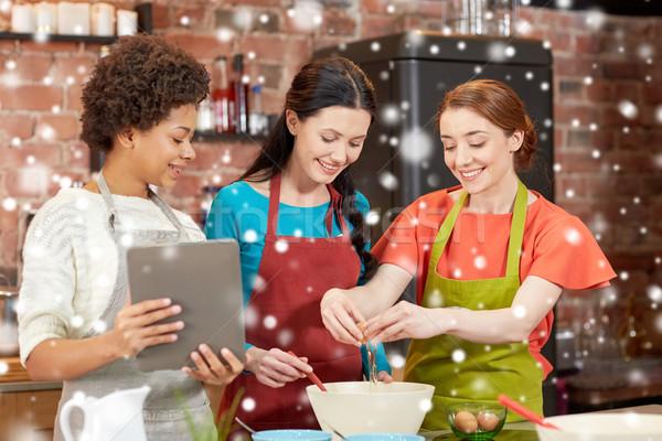 happy women with tablet pc in kitchen Stock photo © dolgachov