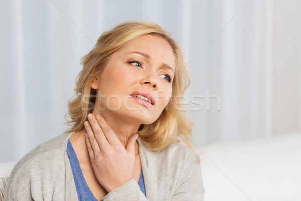 unhappy woman suffering from throat pain at home Stock photo © dolgachov