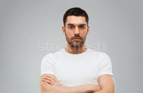 young man with crossed arms over gray background Stock photo © dolgachov