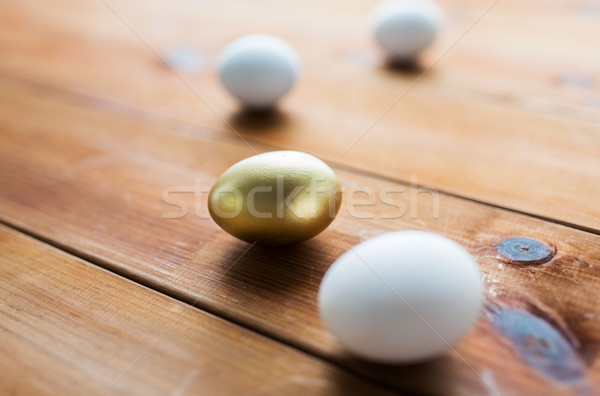 close up of golden and white easter eggs on wood Stock photo © dolgachov