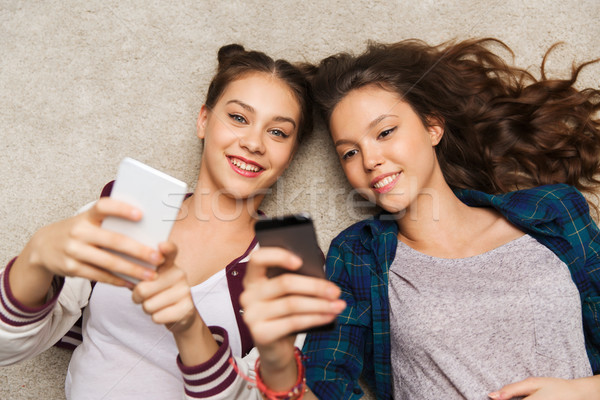 happy teenage girls lying on floor with smartphone Stock photo © dolgachov
