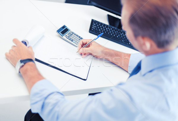 businessman with notebook and calculator Stock photo © dolgachov