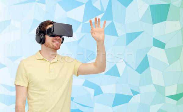 happy man in virtual reality headset or 3d glasses Stock photo © dolgachov