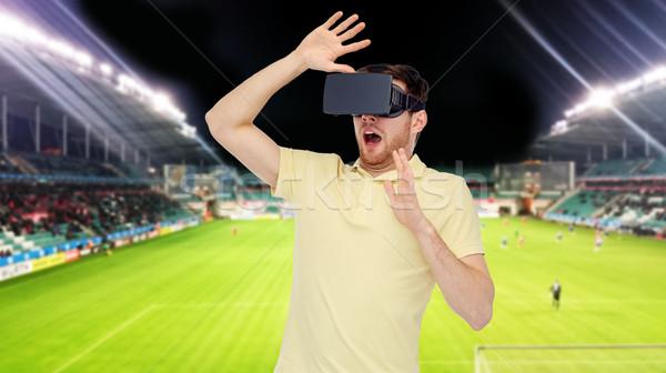 man in virtual reality headset over football field Stock photo © dolgachov