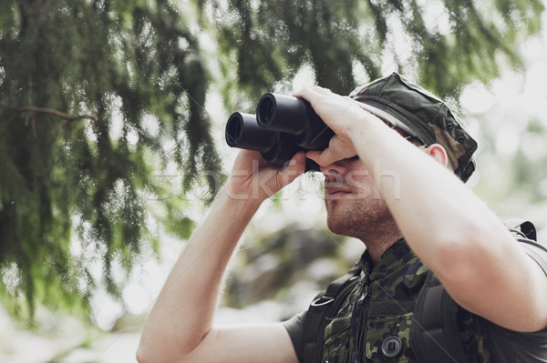 Stock photo: young soldier or hunter with binocular in forest