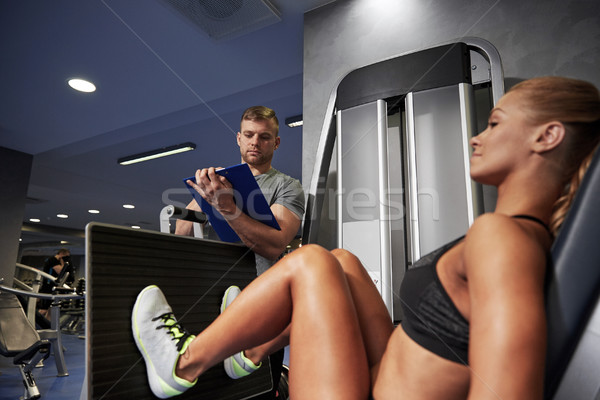 Stock photo: man and woman flexing muscles on gym machine