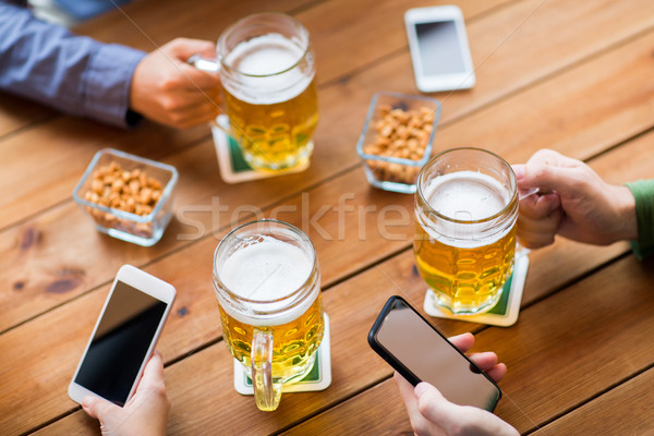 close up of hands with smartphones and beer at bar Stock photo © dolgachov