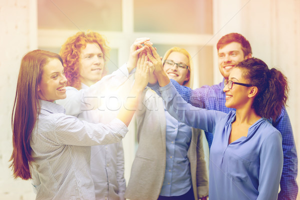 creative team doing high five gesture in office Stock photo © dolgachov