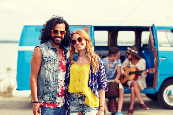 smiling hippie couple with friends over minivan Stock photo © dolgachov