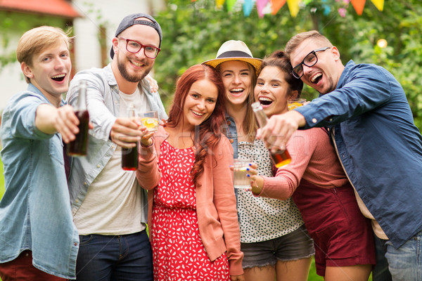 happy friends with drinks at summer garden party Stock photo © dolgachov