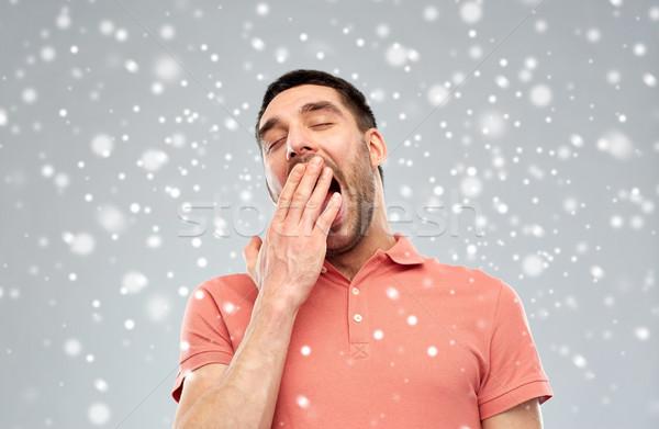 tired yawning man over snow background Stock photo © dolgachov