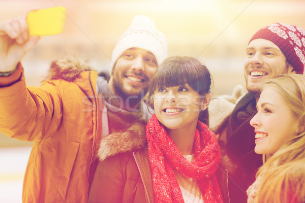 happy friends taking selfie on skating rink Stock photo © dolgachov
