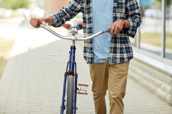 close up of man with bicycle walking along city Stock photo © dolgachov