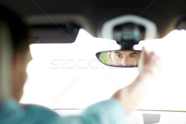 man driving car adjusting rearview mirror Stock photo © dolgachov