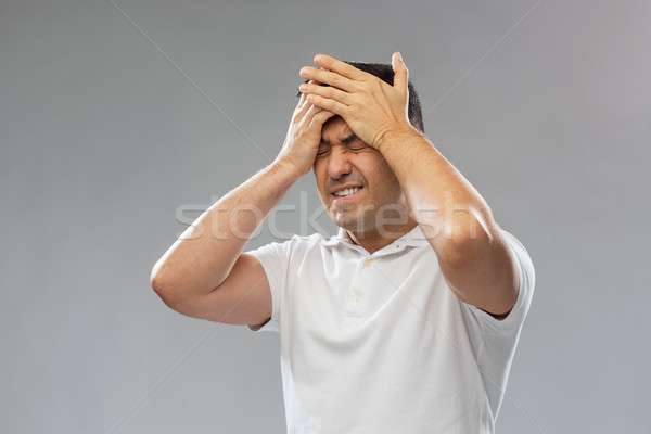 unhappy man suffering from head ache Stock photo © dolgachov