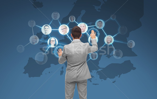 772b51fc businessman using virtual screen with contacts Stock photo © dolgachov