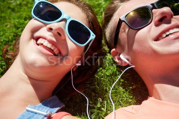 happy teenage couple with earphones lying on grass Stock photo © dolgachov
