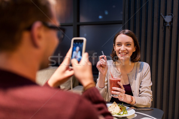happy couple with smartphone at vegan restaurant Stock photo © dolgachov