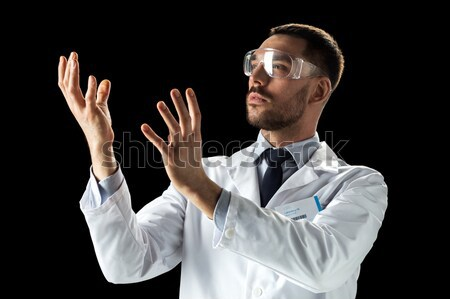 doctor or scientist in lab coat and safety glasses Stock photo © dolgachov