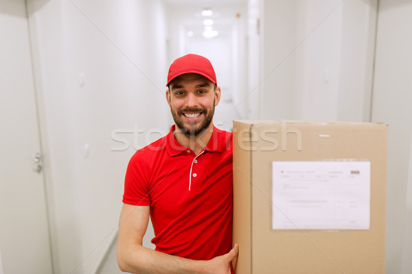 delivery man with parcel box in corridor Stock photo © dolgachov