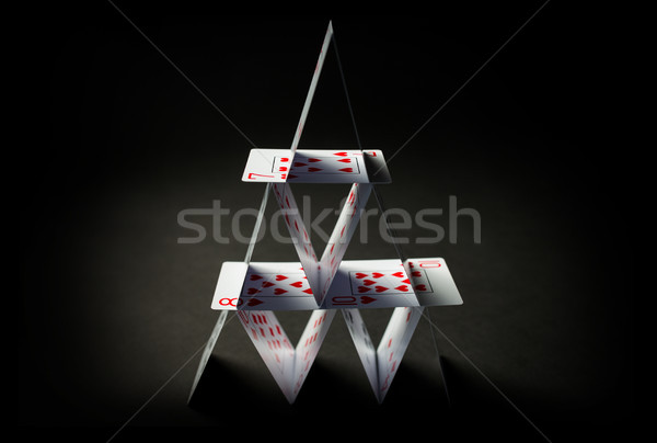 house of playing cards over black background Stock photo © dolgachov